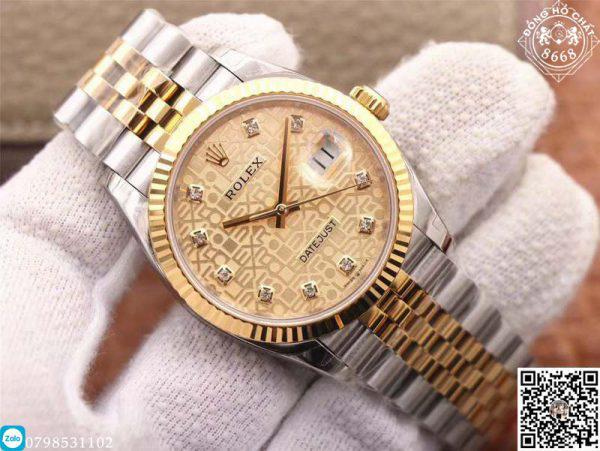 Hoàn thiện núm với chất liệu thép bọc vàng tăng vẻ đẹp hài hòa và đẳng cấp cho đồng hồ. Được thiết kế khía rãnh tỉ mỉ đều đặn. Giúp người dùng dễ dàng thuận tiện trong việc xoay vặn núm. Bên trên núm được khắc sắc nét logo vương miện của thương hiệu Rolex.